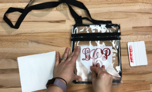 Gently peel EasyPSV Application Tape away from the monogrammed stadium bag