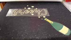 Heat pressing glitter rhinestones to the new year t-shirt