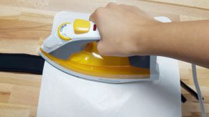 press firmly with the iron to heat apply the HTV