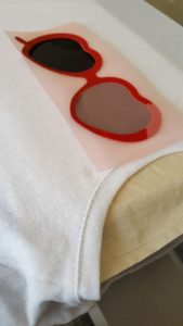 Heat pressing red heart sunglasses frames on a white crop top using red Brick HTV