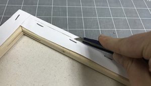 Use an exacto knife to cut the canvas past the stapled edge