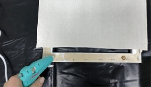 Use a glue gun to re-attach the canvas to the wooden frame