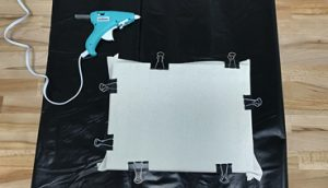 Use binder clips to clamp the canvas down while the glue dries