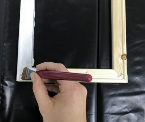 Use a paintbrush to paint the wooden frame with stain or acrylic paint