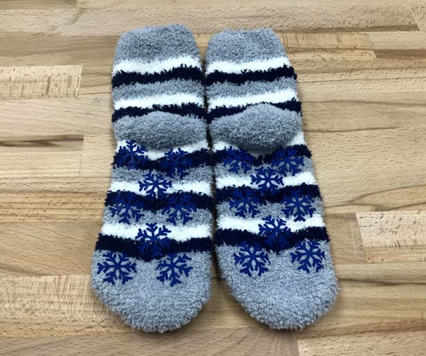 Finished pair of custom fuzzy socks with DIY snowflake sock grips made from Brick 600 iron on vinyl