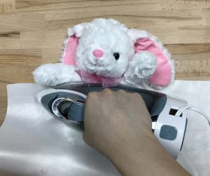 Press the stuffed animal firmly with the home iron